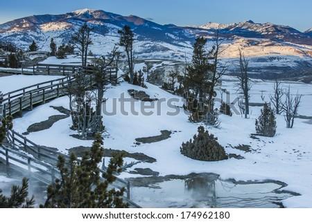 Boardwalk near the geyser at sunset - winter in Yellowstone National Park - stock photo