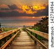 Boardwalk on beach at sunrise - stock photo