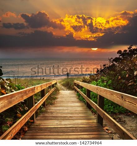 Boardwalk on beach at sunrise - stock photo