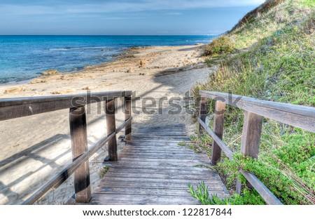 boardwalk to the sea in an hdr environment - stock photo