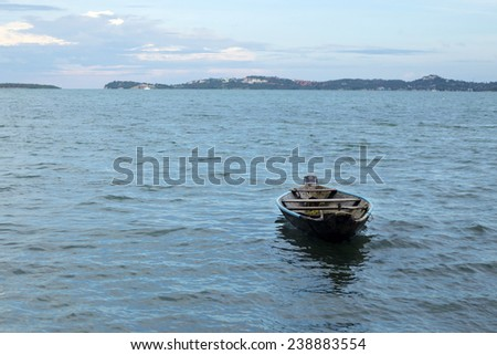 Boat alone on the river forming a clean composition with sea and mountains background - stock photo