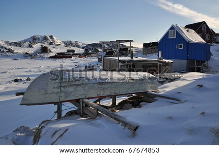 Boat and blue house in the Kulusuk village, winter,Greenland