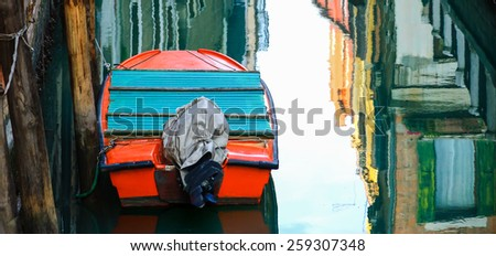 Boat and reflection of colorful houses in the water. Narrow canal in Venice. - stock photo