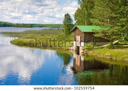Boat and wooden house on the lake in Finland