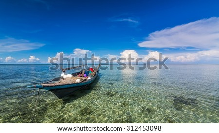 Boat at the beach. Borneo, Sabah, Malaysia Image has grain or blurry or noise and soft focus when view at full resolution. (Shallow DOF, slight motion blur) - stock photo