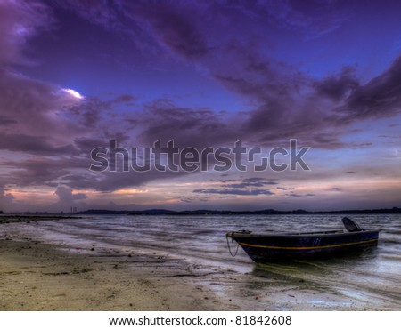Boat Beached at Low Tide, at Day's End, at Twilight. - stock photo