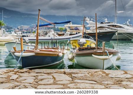 Boat berth yachts tied behind cloudy sky - stock photo