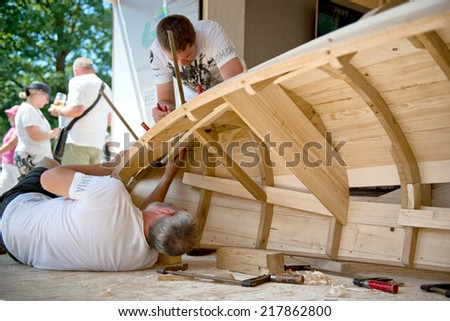 Boat builder at International Danube festival in Ulm, Germany working on the wooden frame of a boat watched by a group of spectators - stock photo