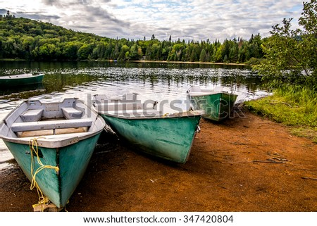 Boat by deck on a lake in National Park Mont Tremblant, Canada. Travel, explore, adventure, vacation, summer, wilderness, retirement, fishing and concept. - stock photo