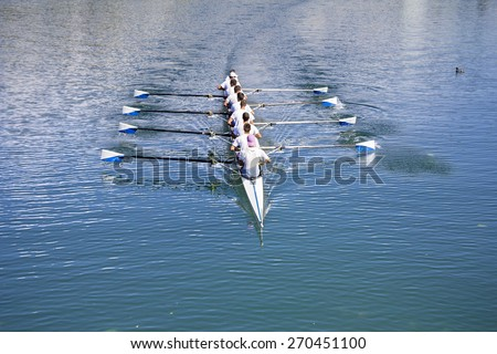 Boat coxed eight Rowers rowing on the blue lake  - stock photo