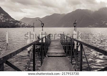 Boat dock in Lugano, Switzerland. Nautical, travel, European vacation, boating and yachting concept. Black and white. High contrast - stock photo