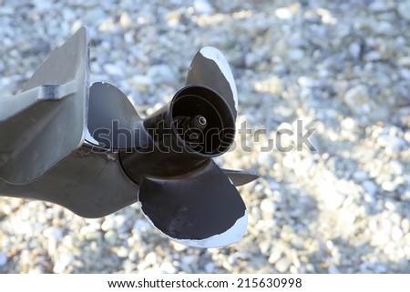 Boat engine propeller. Boat propeller on the sand beach. - stock photo