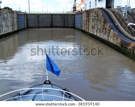 Boat entering the locks on the Panama Canal, with gate visible from the deck - stock photo