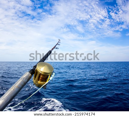 Boat fishing rods over a beautiful cloudy seascape - stock photo