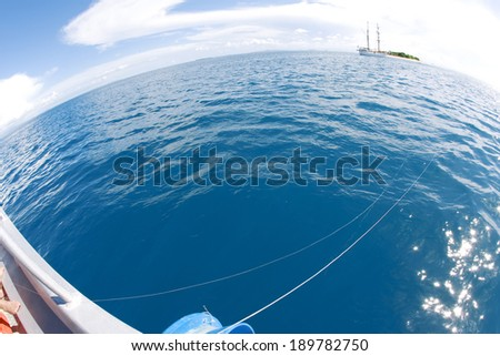 Boat floating on water with fishing line out into the ocean  - stock photo