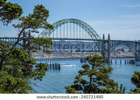 Boat going under the Yaquina Bay Bridge in Newport, Oregon - stock photo