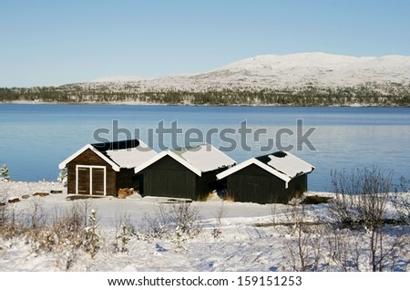 Boat houses by a lake in winter