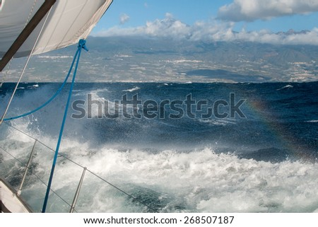 Boat in a stormy ocean is coming to Tenerife Islands with the volcano El Teide.