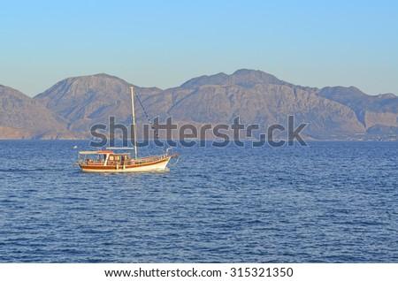 boat in agios nikolaos port, Crete Island, Greece, with blue sky and mountain background. - stock photo