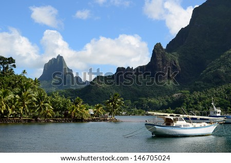 Boat in Cooks Bay with Moua Puta mountain in the background on the tropical pacific island of Moorea, near Tahiti in French Polynesia. - stock photo