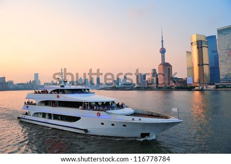 Boat in Huangpu River with Shanghai urban architecture - stock photo