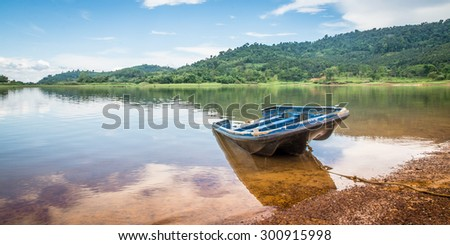 boat in landscape of lake  with mountain and blue sky