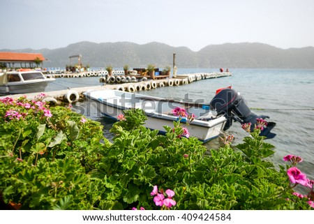 Boat in the harbor of the Mediterranean sea, the flowers and the blue sea, relaxation and sea air. Great place for a summer vacation. - stock photo