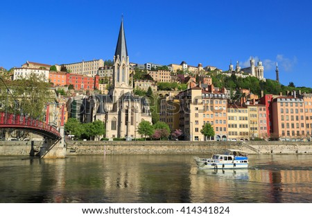 Boat in the Saone rivier in front of the Church of Saint Georges, Lyon, France. - stock photo