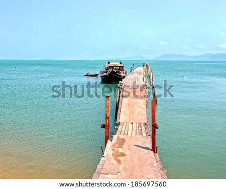 boat is docking at a old wooden pier at the island of koh samui , Thailand  - stock photo
