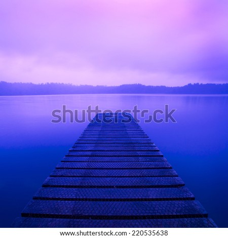 Boat jetty and a calm lake at sunrise, New Zealand. - stock photo