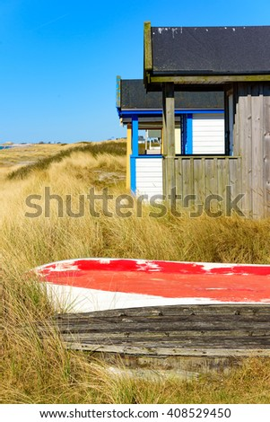 Boat keels in the grass beside a bathing hut at a beach one sunny and fine day. - stock photo