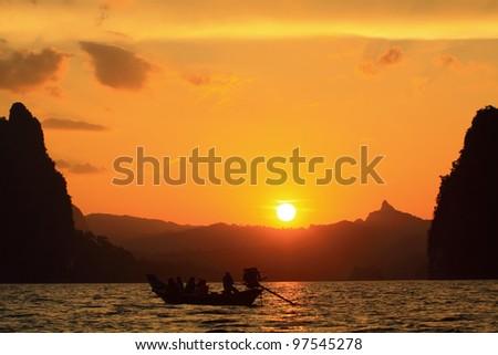 Boat looking sunset on lake - stock photo