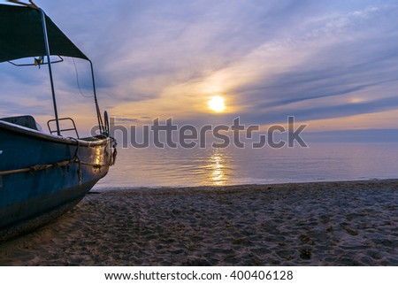 Boat lying on the seaside with the sun and clouds on the horizon in the fog. The characteristic soft blur.