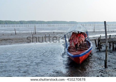 Boat moored at the pier during low tide in evening day - stock photo