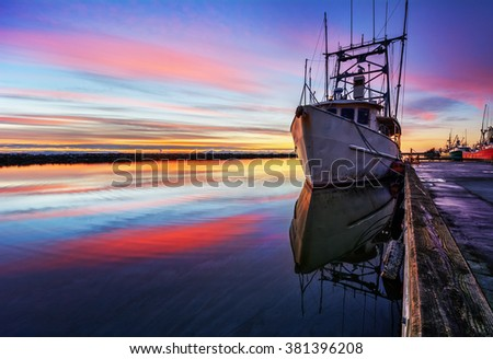 Boat moored on the calm river, against the vibrant sunset - stock photo