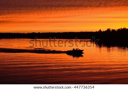 Boat Motoring After Sunset on a Calm Lake