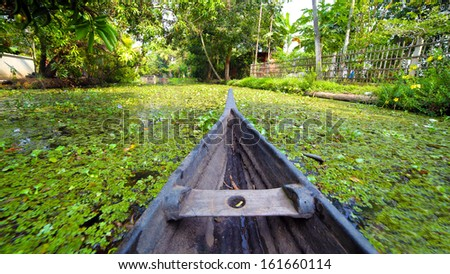 Boat moving along canal at sunset in Kerala Backwaters - stock photo