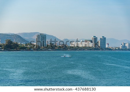 Boat moving on the sea with cityscape on the background. Hua Hin, Thailand