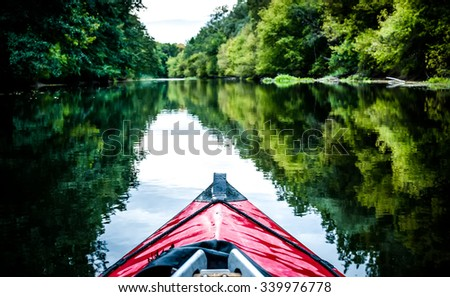 boat nose on a calm river background - stock photo