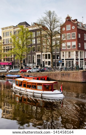 Boat on a canal and historic terraced houses in the city of Amsterdam, Netherlands, North Holland province. - stock photo