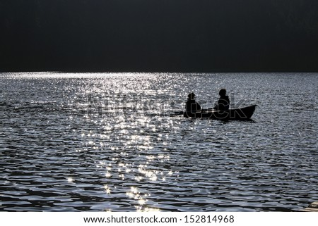 Boat on a lake in dusk - stock photo
