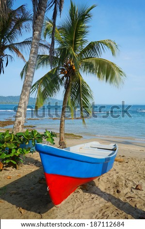 Boat on a tropical beach with coconut tree and the Caribbean sea in background, Puerto Viejo de Talamanca, Costa Rica, Central America - stock photo