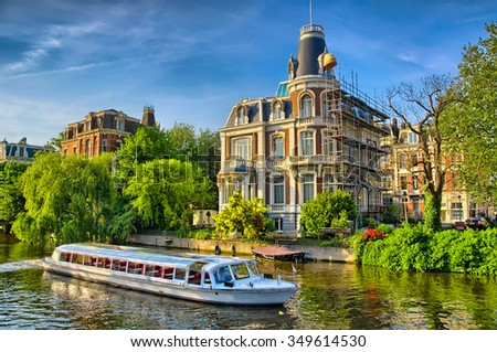 Boat on Amstel river near beautiful houses in Amsterdam, Holland, Netherlands, HDR - stock photo