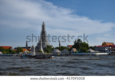 boat on Chaophraya River in front Wat Arun and blue sky, Temple of Dawn, Bangkok, central of Thailand  - stock photo