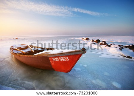 Boat on ice. Winter landscape composition. - stock photo