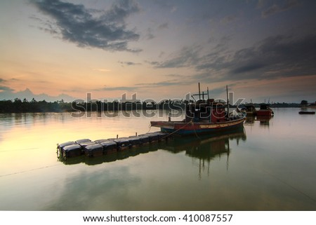 Boat on lake with a reflection in the water at sunrise taken with Slow Shutter. Motion Blur, Soft Focus due to Slow Shutter Speed. Copy Space Area