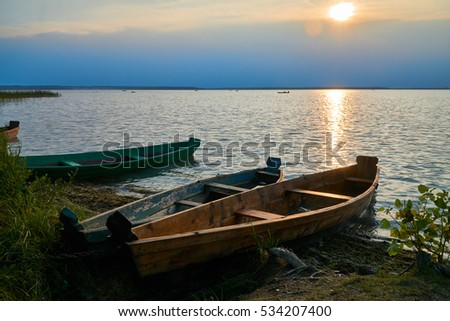 Boat on large lake in the evening sunset.