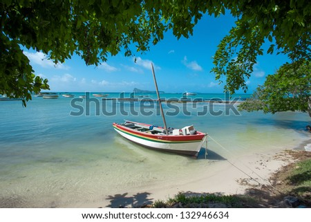 Boat on paradise white sand beach and palm tree of a tropical is