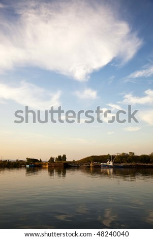 Boat on River Channel with Sun and Clouds