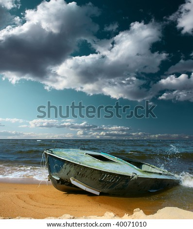 Boat on seaside with strong wind and storm clouds - stock photo